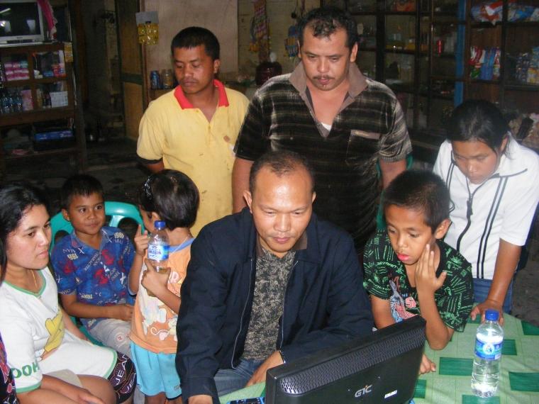 Petrus Sitohang sedang melatih cara menggunaka internet kepada anak-anak dan pemuda Palipi yang menyambut dengan antusias. (Photo: Rudy Sitohang)